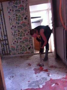 Elina spättar bort golv i hallen